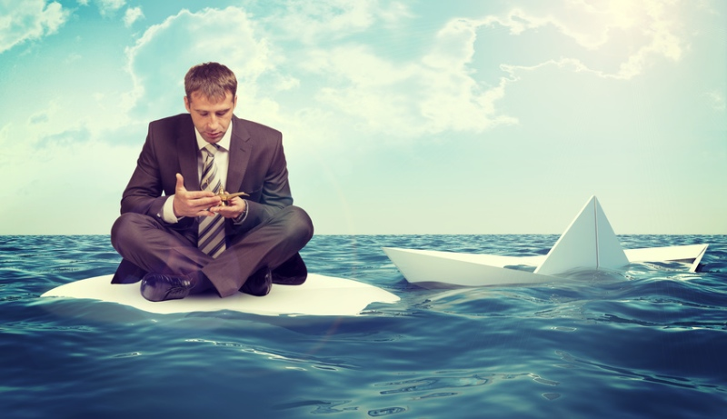 Man on raft in sea with smart phone