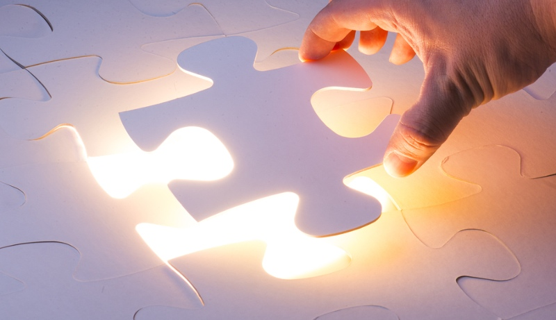 Hand placing correct piece into a puzzle on glowing background