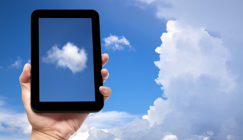 Hand holding tablet amongst the clouds